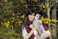Beautiful brunette woman smiling and hugging her little cute white dog Stock Images