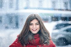 Beautiful brunette woman smiling and rejoices to snow at dte city street.  Stock Image