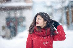 Beautiful brunette woman smiling and rejoices to snow at dte city street.  Royalty Free Stock Photography