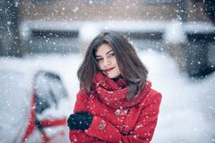 Beautiful brunette woman smiling and rejoices to snow at dte city street.  Royalty Free Stock Images