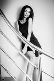 Beautiful brunette woman on the stairs in a black dress in black Stock Photos