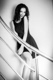 Beautiful brunette woman on the stairs in a black dress smiling Royalty Free Stock Images