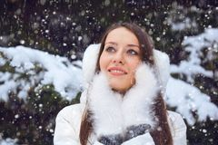 Beautiful brunette woman standing under snowfall Royalty Free Stock Photo