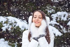 Beautiful brunette woman standing under snowfall Stock Photo