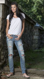 Beautiful brunette woman standing in white t-shirt and jeans - garden Stock Photos