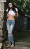 Beautiful brunette woman standing in white t-shirt and jeans - garden Royalty Free Stock Photography