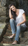 Beautiful brunette woman standing in white t-shirt and jeans - garden Royalty Free Stock Image
