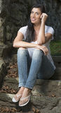 Beautiful brunette woman standing in white t-shirt and jeans - garden Stock Images