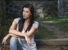 Beautiful brunette woman standing in white t-shirt and jeans - garden Stock Photo