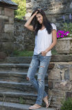 Beautiful brunette woman standing in white t-shirt and jeans - garden Royalty Free Stock Images