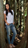 Beautiful brunette woman standing in white t-shirt and jeans - woods Royalty Free Stock Image