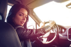 Beautiful brunette woman steers car expensive car Stock Photos