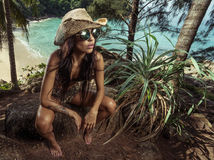 Beautiful brunette woman with straw hat and sunglasses in tropical forest Stock Photo