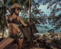 Beautiful brunette woman with straw hat and sunglasses in tropical forest Royalty Free Stock Photography