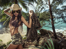 Beautiful brunette woman with straw hat and sunglasses in tropical forest Royalty Free Stock Photos