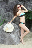 Beautiful brunette woman in sunglasses and with hat stands Stock Photography