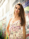 Beautiful brunette woman at sunny day against graffiti wall Royalty Free Stock Images