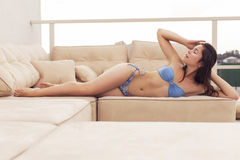 Beautiful brunette woman in swimsuit on the beach alone relaxing Royalty Free Stock Photography