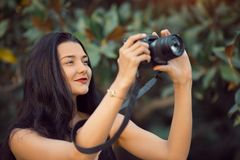 Beautiful Brunette Woman Taking a Picture Outdoor by Digital Camera royalty free stock image