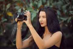 Beautiful Brunette Woman Taking a Picture Outdoor by Digital Camera stock images
