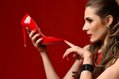 Beautiful brunette woman touch with finger red shoe high hill on dark red. Background Royalty Free Stock Images