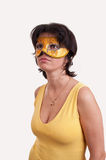 Beautiful brunette woman trying a mysterious golden carnival mask Royalty Free Stock Image