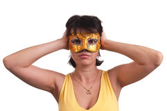 Beautiful brunette woman trying a mysterious golden carnival mask Stock Photos