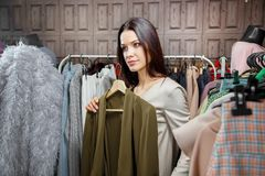 Beautiful brunette woman trying new dress in clothing shop before mirror. Shopping and consumerism concept.  Royalty Free Stock Photo