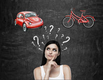 A beautiful brunette woman is trying to chose the most suitable way for travelling or commuting. Two sketches of a car and a bicyc Stock Photo