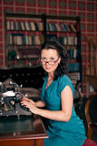 Beautiful brunette woman typewritingin the library. old style photo Royalty Free Stock Images