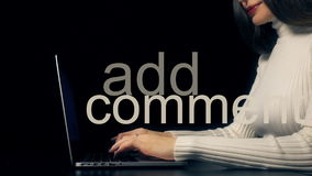 Beautiful brunette woman typing on her laptop against black background. Add comment inscription Royalty Free Stock Photo