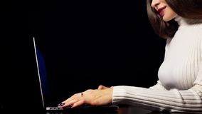 Beautiful brunette woman typing and using trackpad of her laptop. Isolated against black background. 4K video stock video