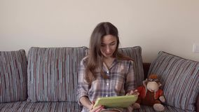 Beautiful brunette woman using her tablet PC at home. 4K close up steadicam video stock video