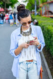 Beautiful brunette woman using smart phone in the city. Through glasses royalty free stock images