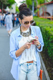 Beautiful brunette woman using smart phone in the city. Through glasses Royalty Free Stock Photography
