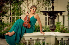 Beautiful brunette woman with a violin in her hands. plaza Royalty Free Stock Images