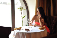 Beautiful brunette woman waiting at the table in restaurant.  royalty free stock image