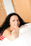 Beautiful brunette woman wakes up Stock Photography