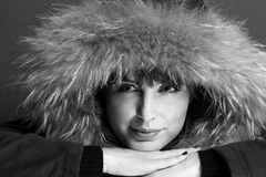 Beautiful brunette woman wearing fur hoodie Stock Photo