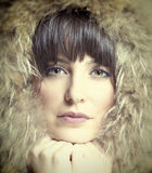 Beautiful brunette woman wearing fur hoodie Stock Photography
