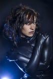 Beautiful brunette woman wearing latex dress on dark background, Stock Photo