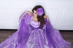 Beautiful brunette woman wearing in purple dress leaning on mode Royalty Free Stock Images
