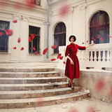 Beautiful brunette woman wearing red dress, standing on stairs. Beautiful brunette woman wearing red dress, standing on the stairs of the vintage building. Rose Royalty Free Stock Photography