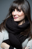 Beautiful brunette woman wearing scarf and sweater. Looks at camera Royalty Free Stock Image