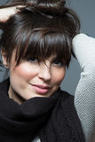 Beautiful brunette woman wearing scarf and sweater. Looks at camera Royalty Free Stock Photos