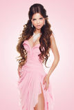 Beautiful brunette woman wearing in sexy luxury dress over pink Stock Image