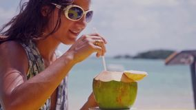 Beautiful brunette woman wearing sunglasses drinking fresh coconut water with straw on the beach fun vacation. Slow stock video footage