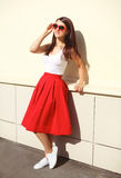 Beautiful brunette woman wearing a sunglasses and red skirt Stock Image