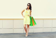 Beautiful brunette woman wearing yellow dress with shopping bags in city Stock Photos