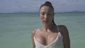 Beautiful girl on tropical island. Beautiful brunette woman in white dress looking into the camera while walking in the sea water over blue sky background stock video